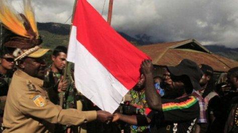 Bupati Puncak, Willem Wandik (kiri) menyerahkan bendera merah putih ke pimpinan Kelompok Kriminal Bersenjata dari kelompok Sinak-Yambi, Utaringgen Telenggen (kanan)