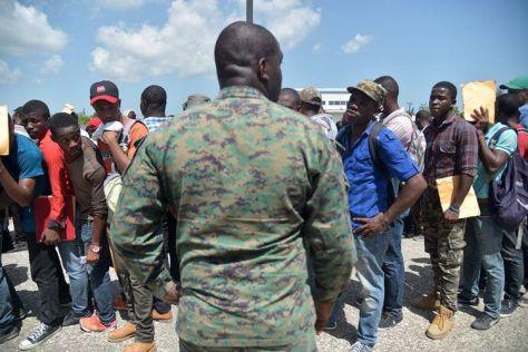 Seorang personel militer Haiti mengawasi barisan para pemuda yang mendaftar untuk bergabung dengan angkatan bersenjata. (AFP)