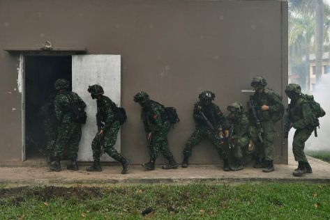 A mixed squad of Singapore Army (right) and TNI-AD soldiers storming a building during Exercise Safkar Indopura, on Nov 20, 2017. [LIM YAOHUI]