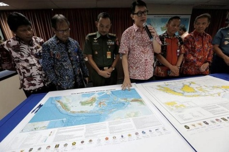 Indonesian Deputy Minister for Maritime Affairs Arif Havas Oegroseno stands in front of a new map of Indonesia during talks with reporters in Jakarta