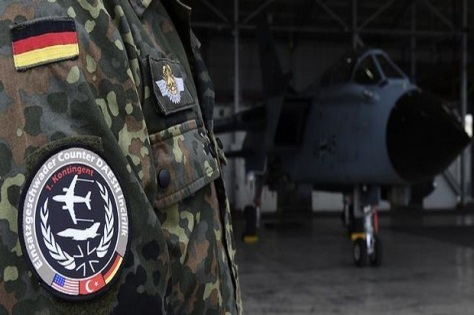 A soldier of the German Armed Forces Bundeswehr wears a patch of the combat wing Counter DAESH Incirlik next to a German Tornado jet in a hangar before a statement of the German and Turkish defence ministers at the air base in Incirlik