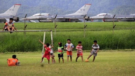 Anak-anak sedang bermain sepak bola di lapangan Dirgantara yang berada dekat landasan pesawat tempur F-16 pangkalan TNI AU, Minggu (11032018). (Tribun Manado)